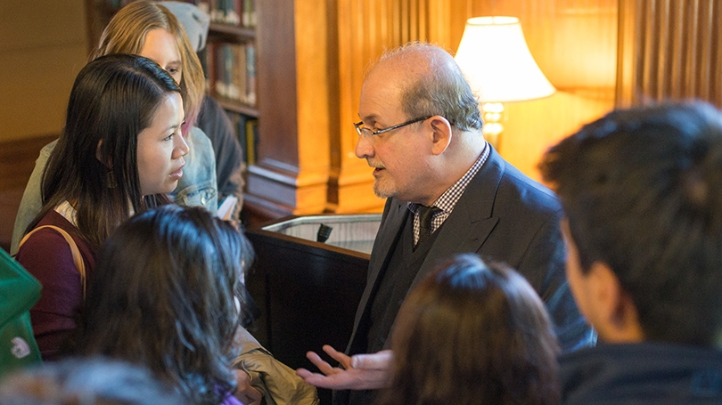 Salman Rushdie surrounded by a group of students